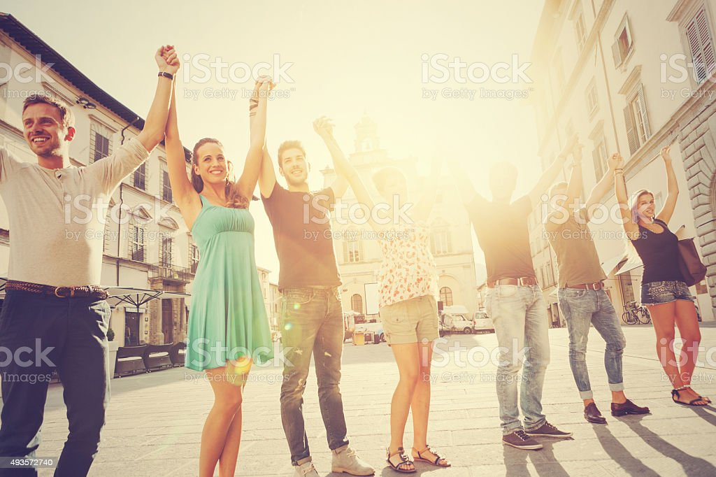 Group of friends with raised arms together stock photo