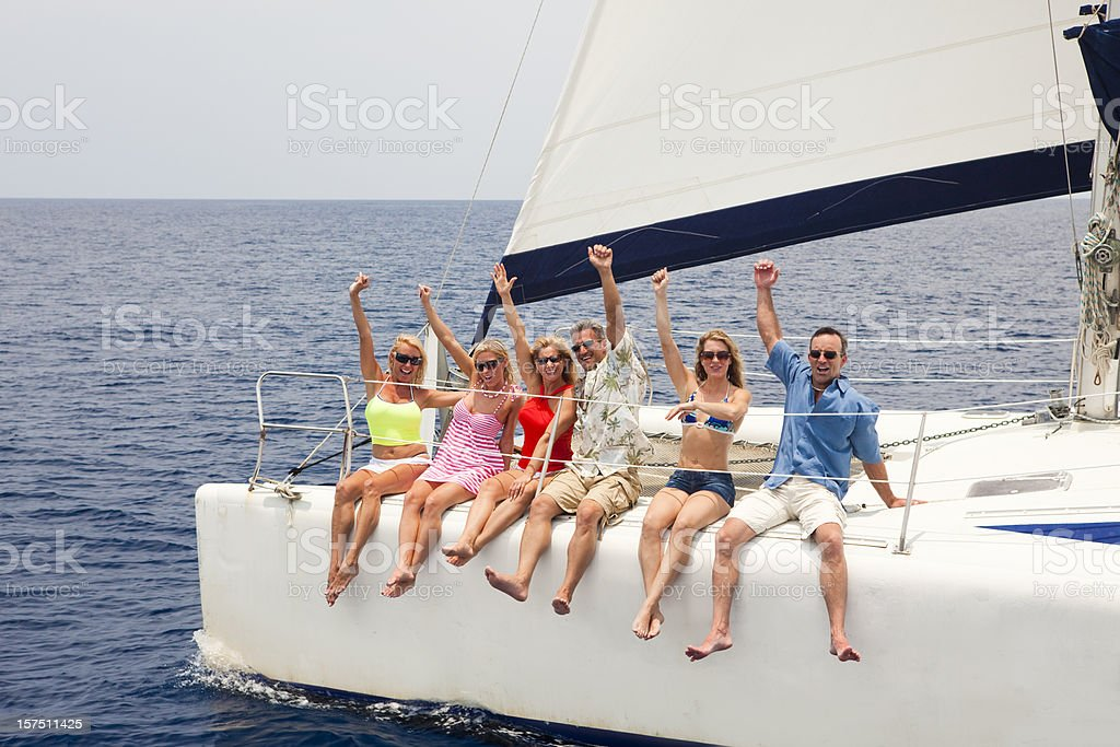 Group of friends yelling and enjoying sailing catamaran stock photo