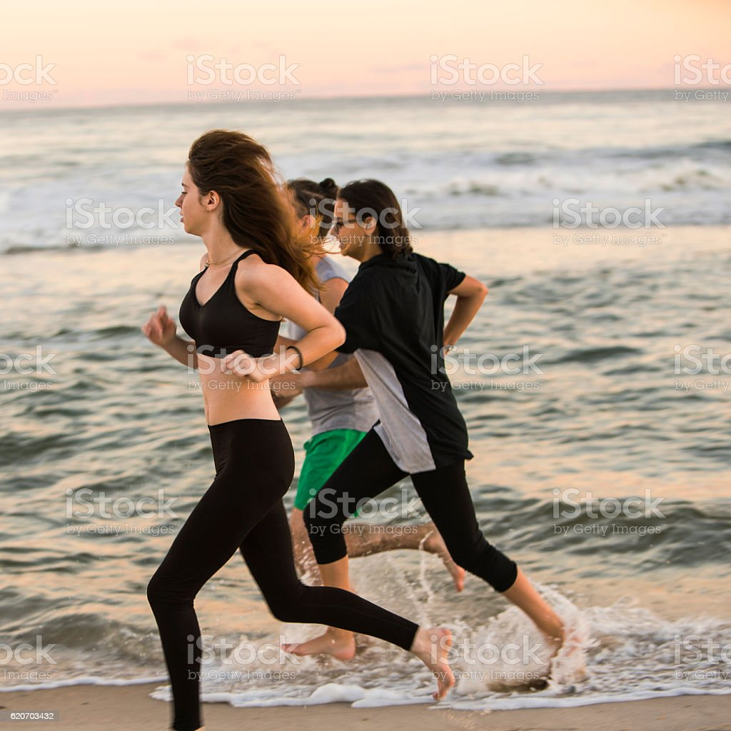 Group of friends, young man and two girls, running beach stock photo