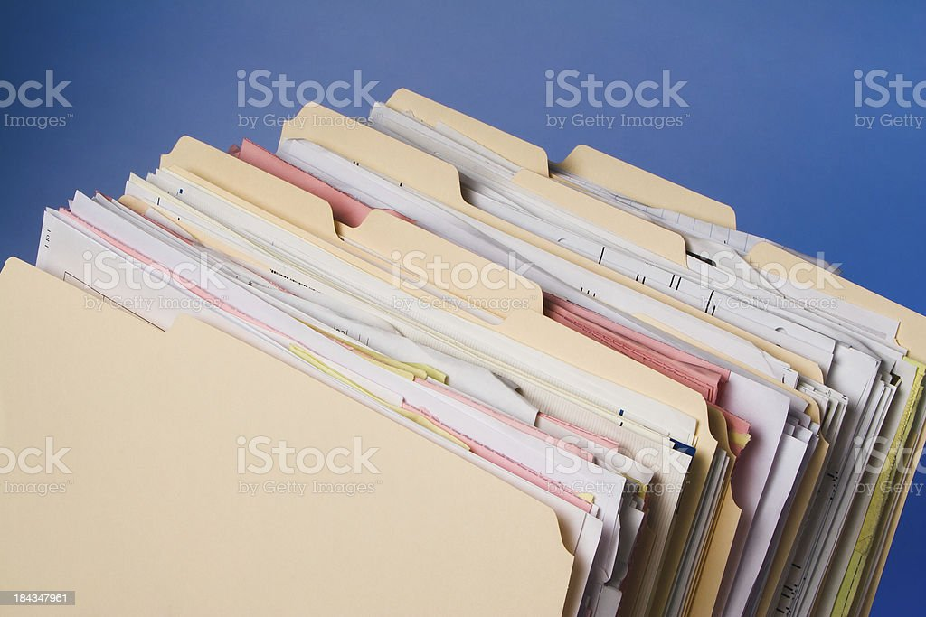 Group of full Manila folders in rack on blue background royalty-free stock photo