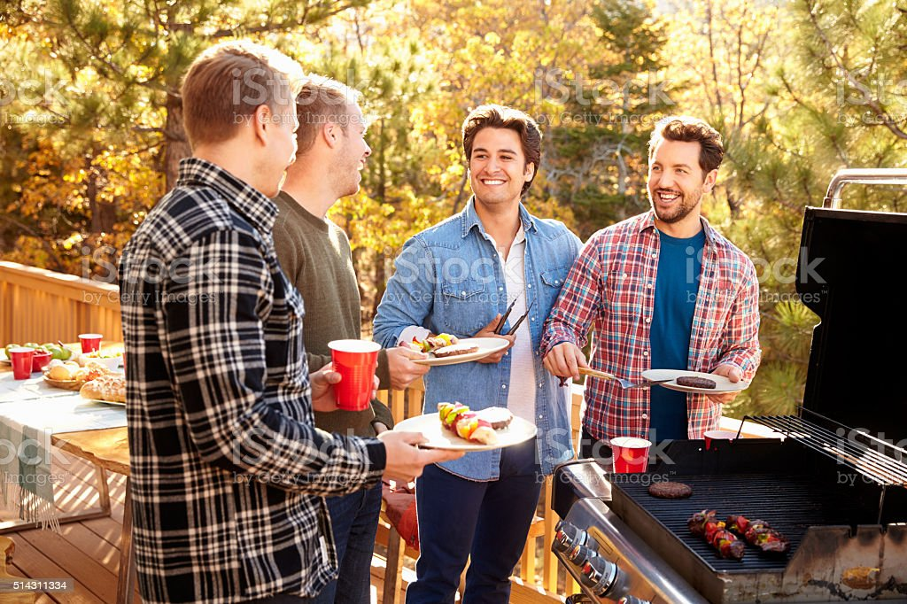 Group Of Gay Male Friends Enjoying Barbeque Together stock photo