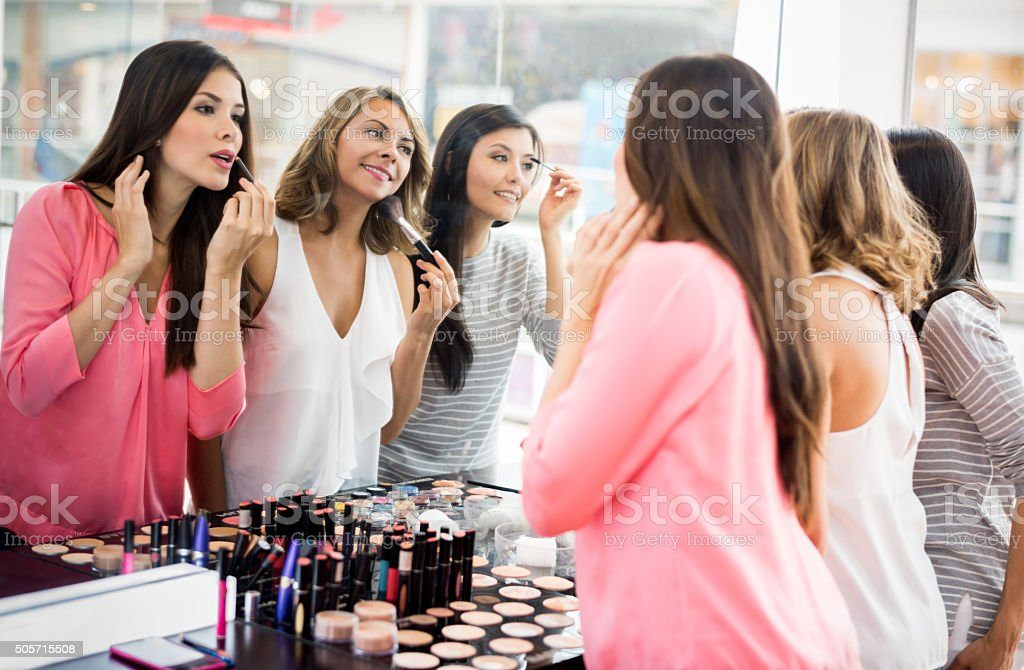 Group of girl friends applying makeup stock photo