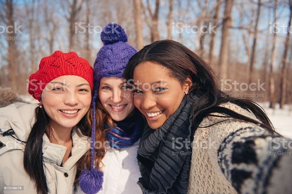 Group of girl friends enjoying taking selfies in the snow stock photo