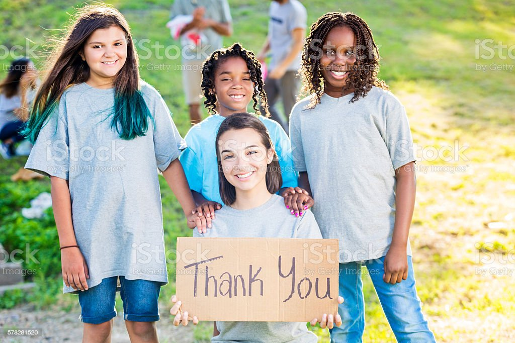 Group of girl volunteers holding up a 'Thank You' sign stock photo