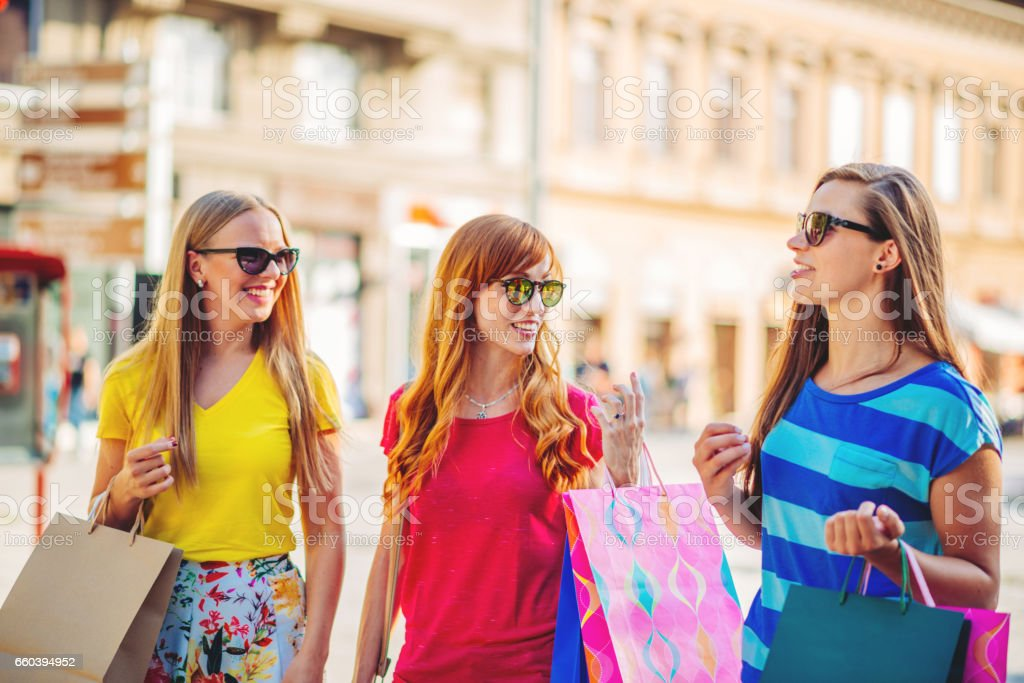 Group of girlfriends enjoying shopping, with shopping bags in city downtown, on sunny summer day in Europe stock photo