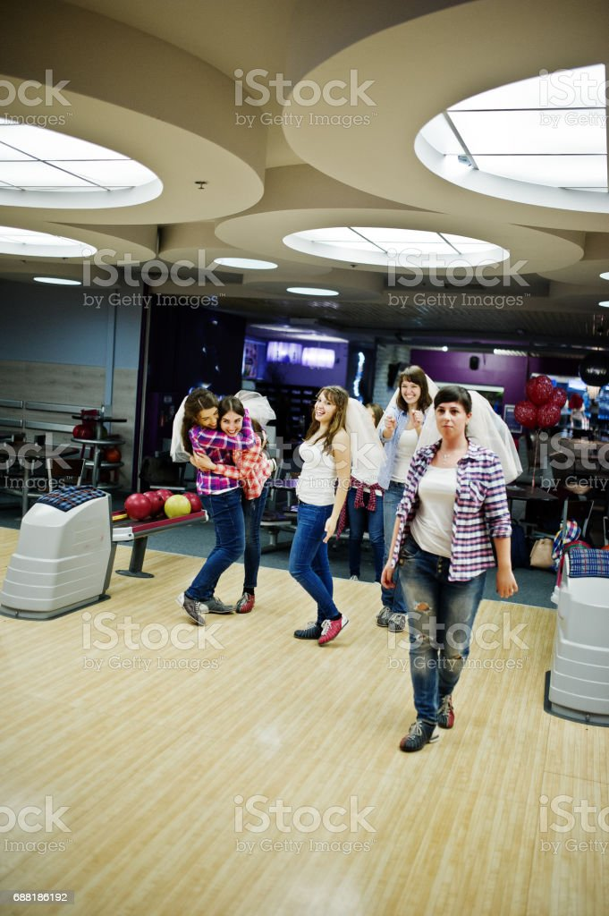 Group of girls having fun and play bowling at hen party. stock photo