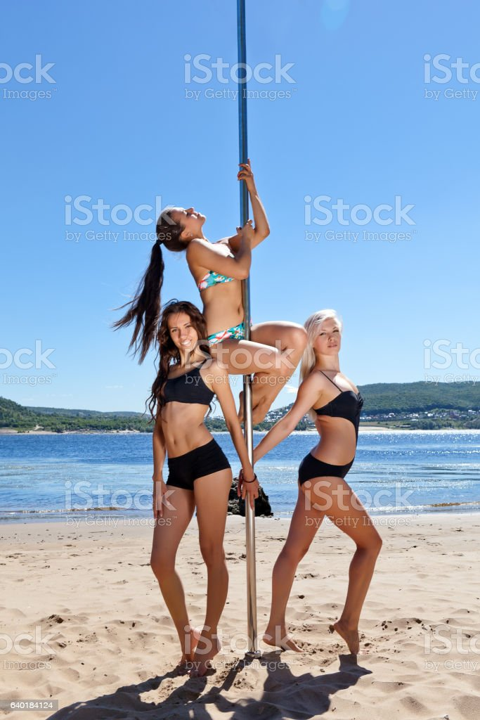 group of girls in bathing suits at pole dancing stock photo