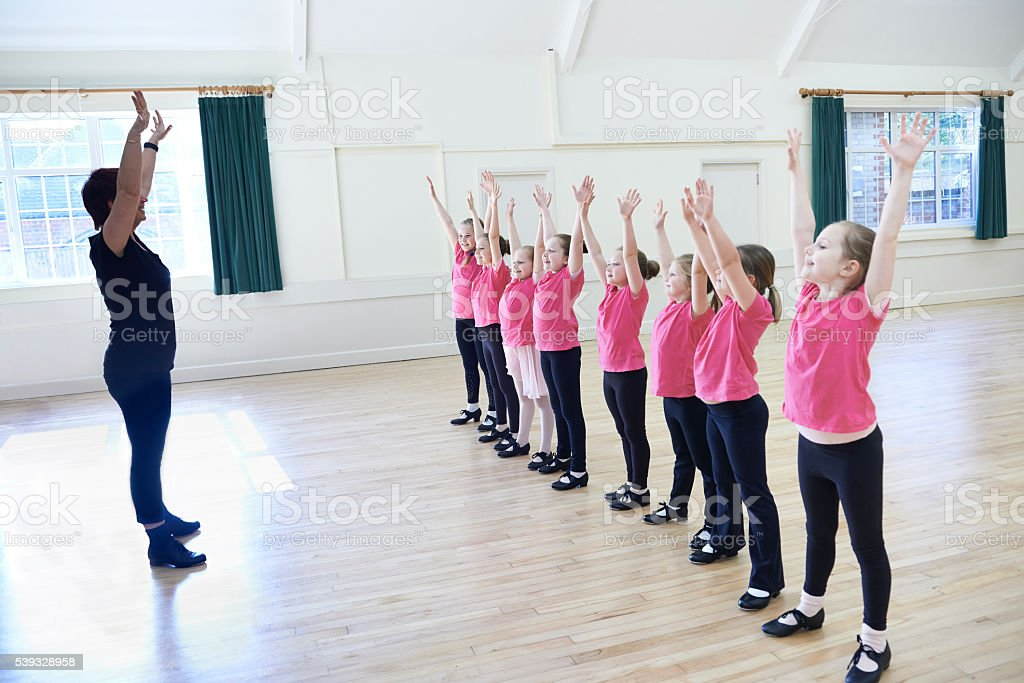 Group Of Girls In Tap Dancing Class With Teacher stock photo