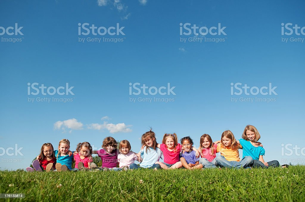 Group of Girls Sitting Outside with Arms Around Each Other royalty-free stock photo