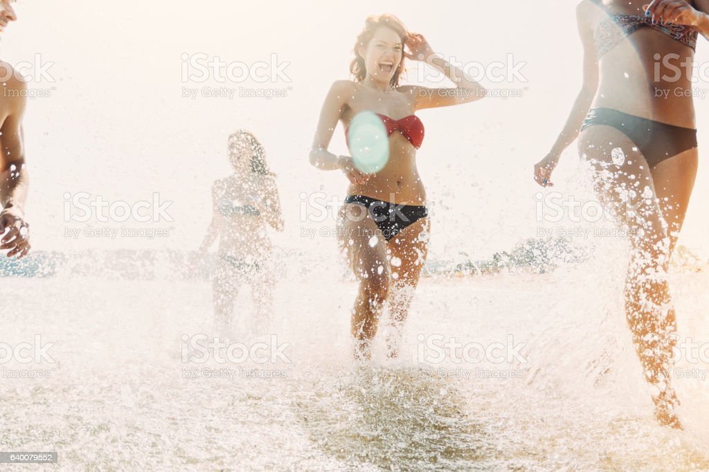 Group of girls splashing in the sea stock photo