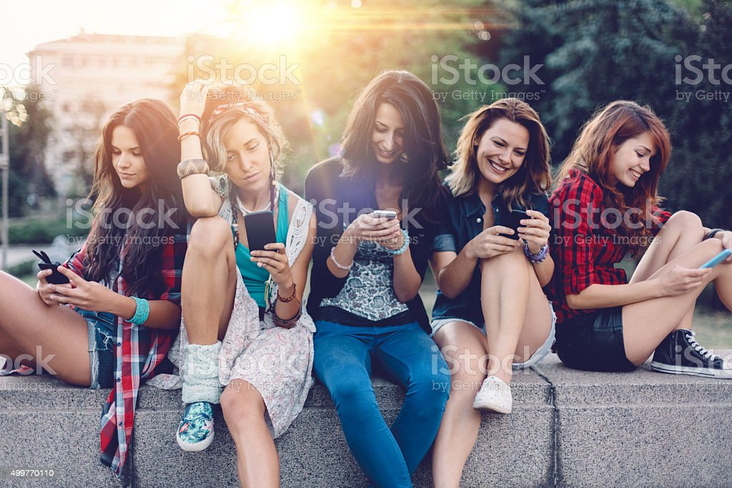 Group of girls texting on smartphones stock photo