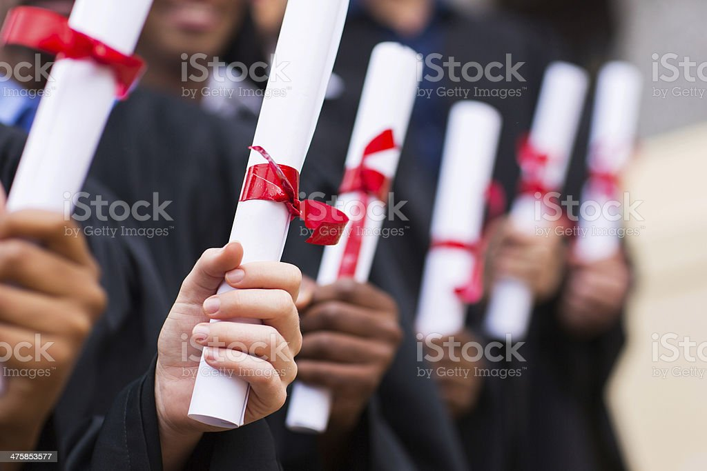 group of graduates holding diploma stock photo