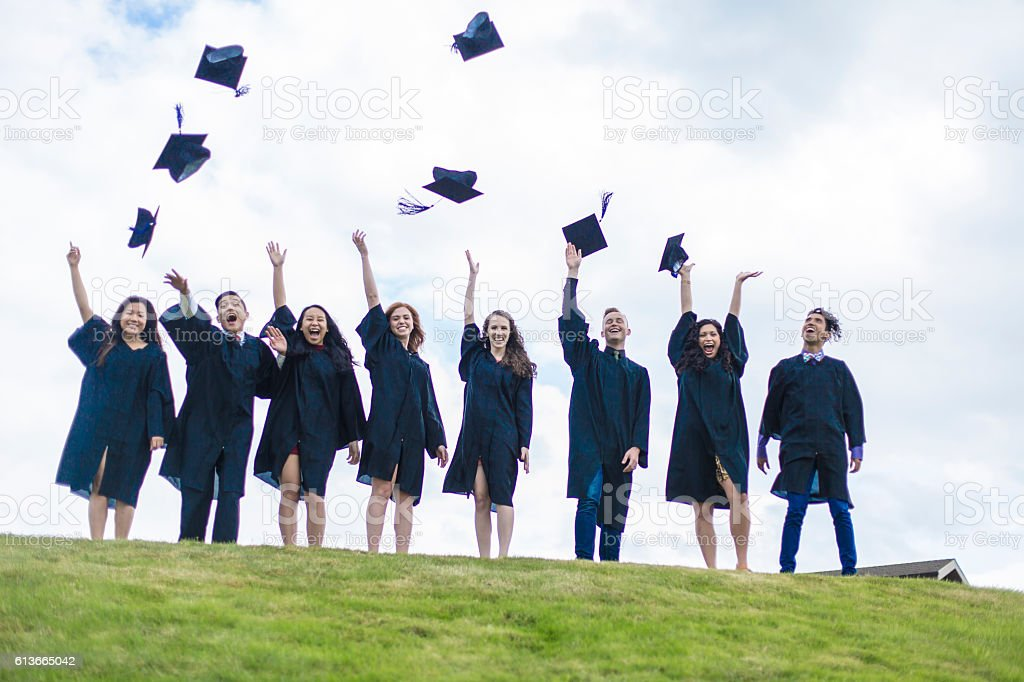 A group of graduates tossing their hats in celebration. stock photo