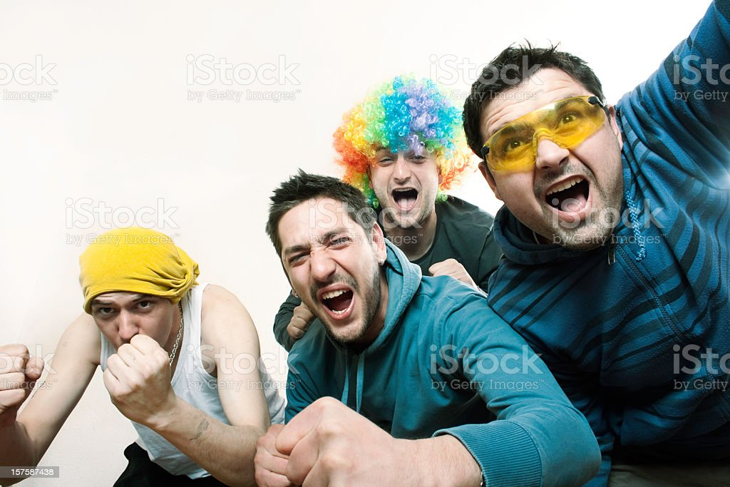 A group of guy sport fans in goofy outfits cheering for team stock photo