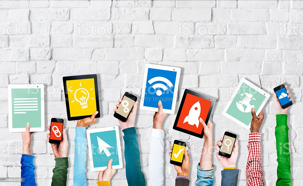 Group of Hands Holding Digital Devices with Symbols stock photo