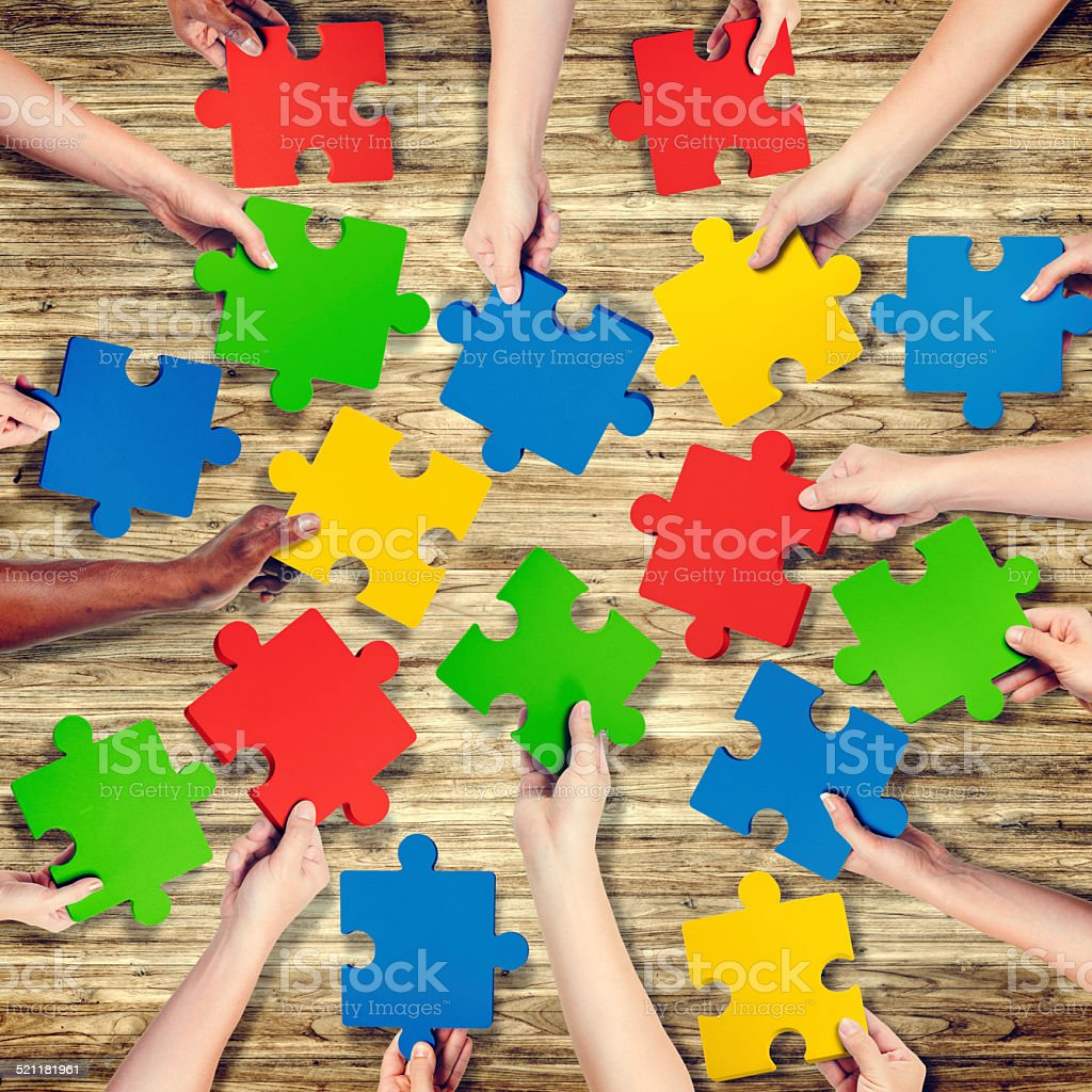 Group of Hands Holding Jigsaw Puzzle stock photo