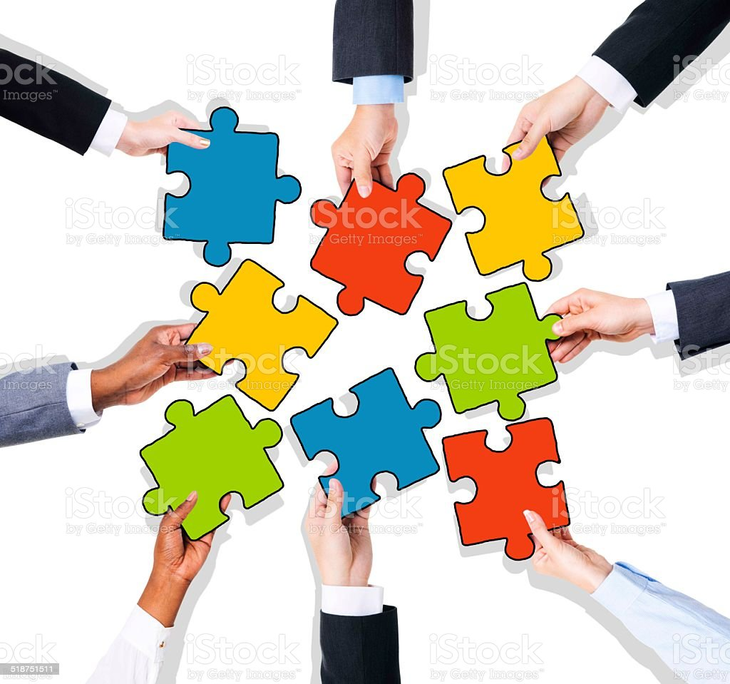 Group of Hands with Jigsaw Puzzle stock photo