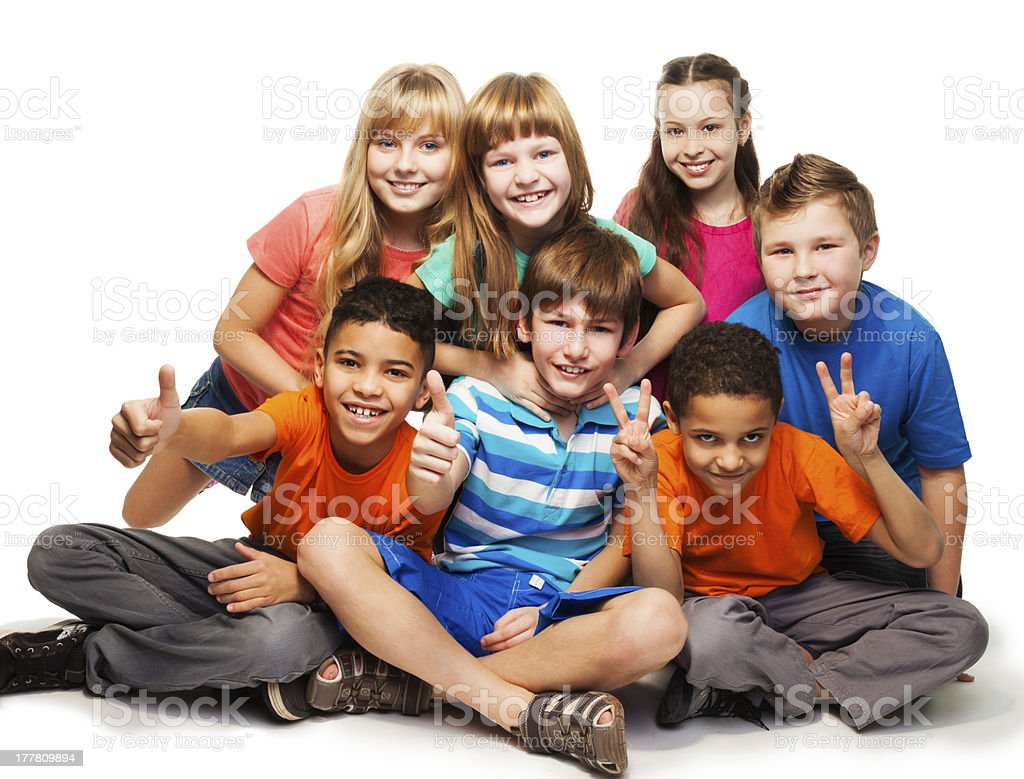 Group of happy boys and girls sitting together stock photo