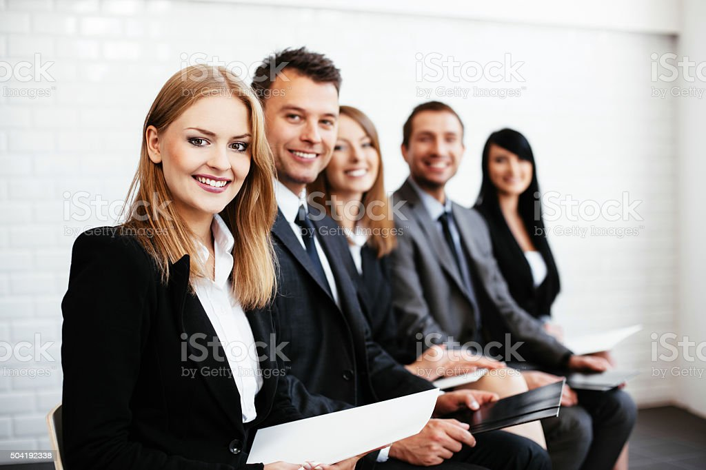 Group of happy business people sitting in a row stock photo