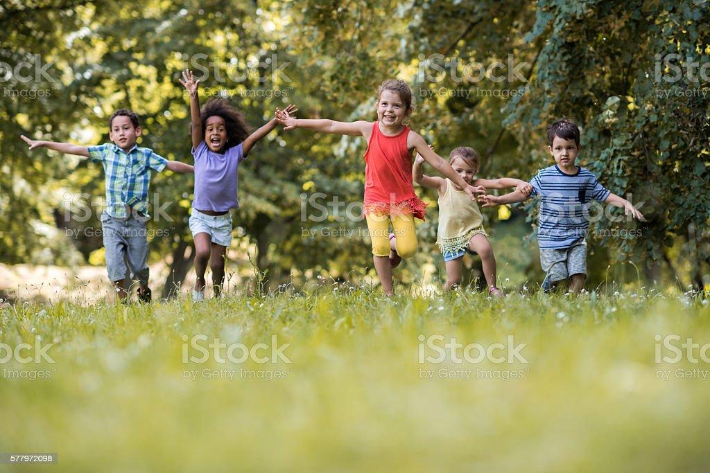 Group of happy children having fun while running in nature. stock photo