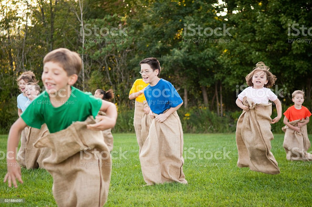 Group of Happy Children Having Potato Sack Race Outside stock photo