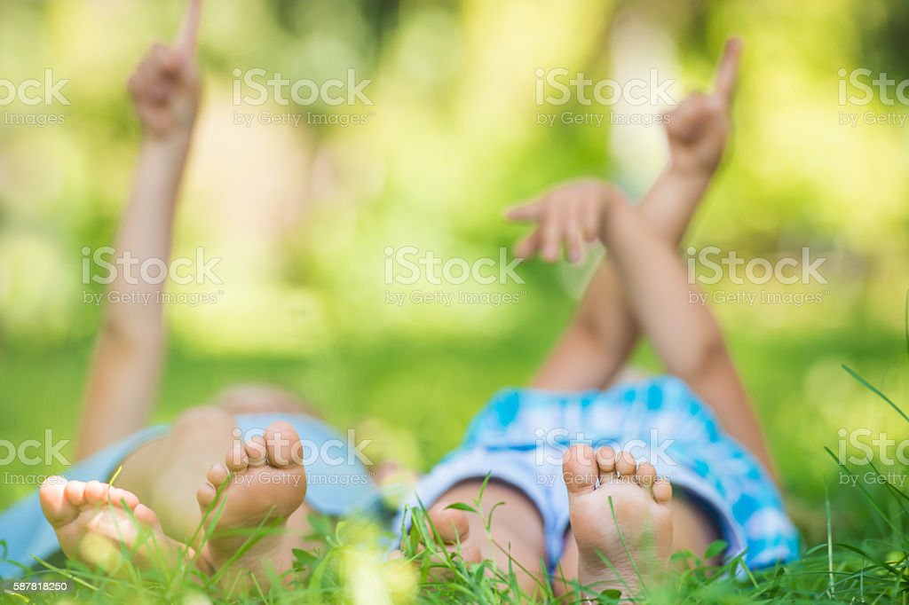 Group of happy children lying on green grass and pointing stock photo