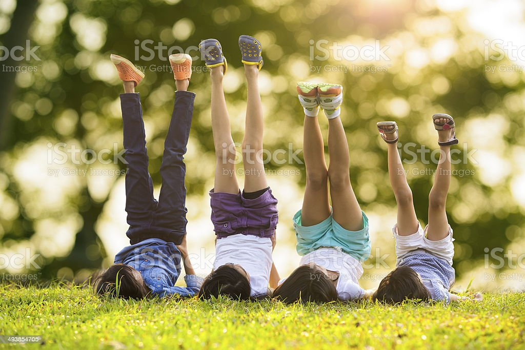 Group of happy children lying on green grass stock photo