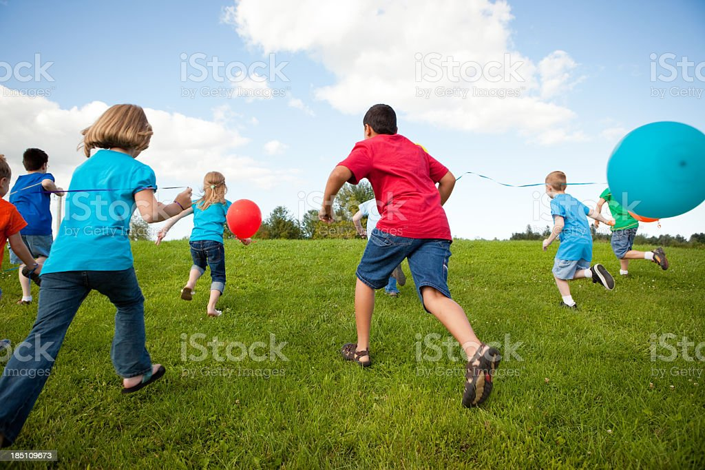 Group of Happy Children Running with Balloons, Color Image royalty-free stock photo
