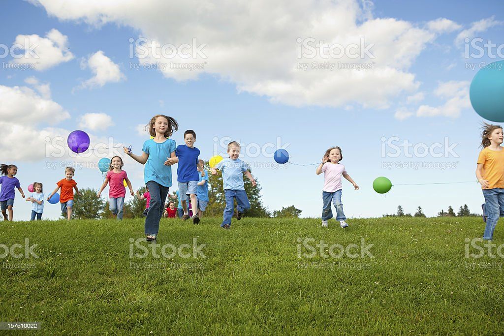 Group of Happy Children Running with Balloons royalty-free stock photo