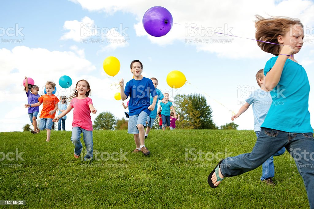 Group of Happy Children Running with Balloons stock photo