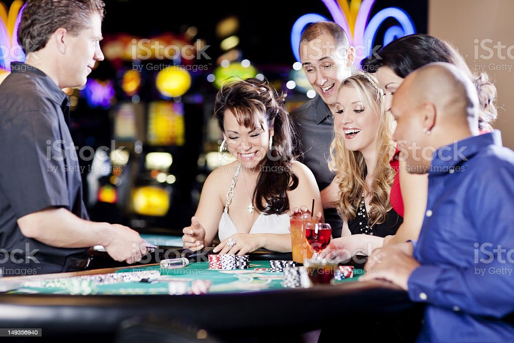 Group of happy diverse people at the blackjack table stock photo
