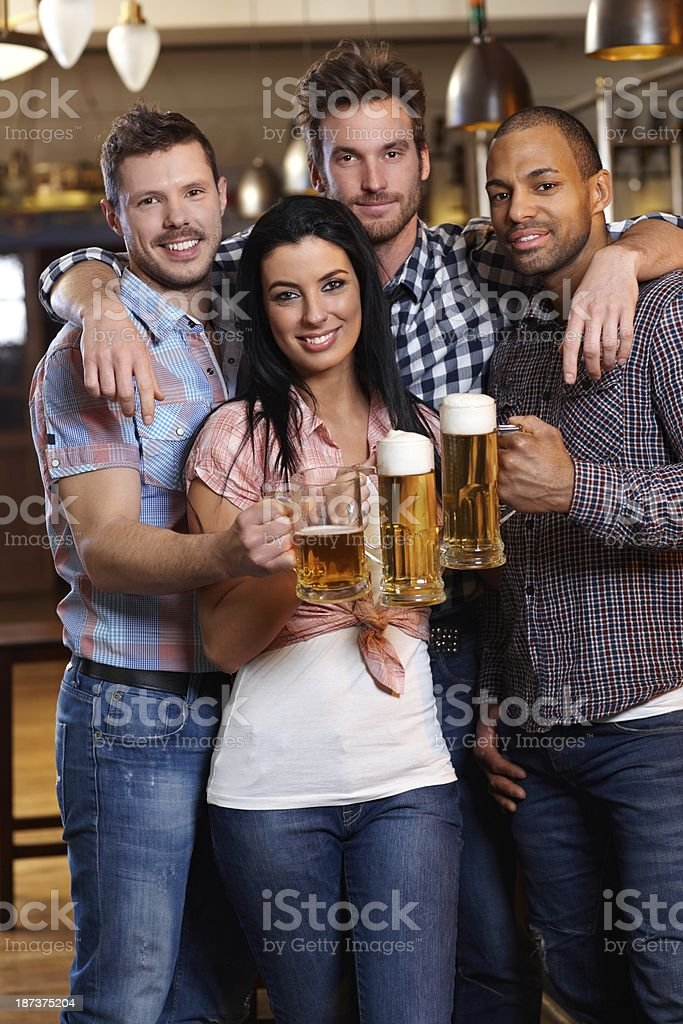Group of happy friends drinking beer at pub stock photo