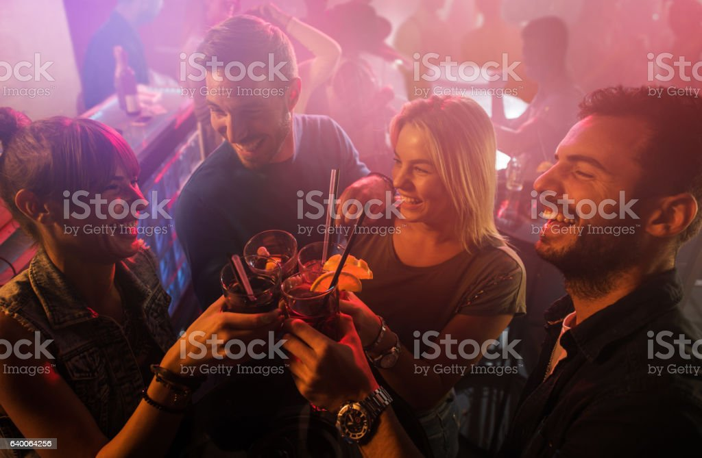 Group of happy friends toasting and celebrating in disco club. stock photo