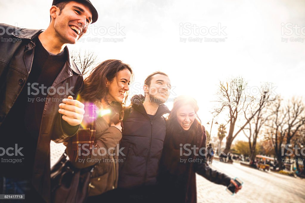 Group of happy friends walking in the city stock photo