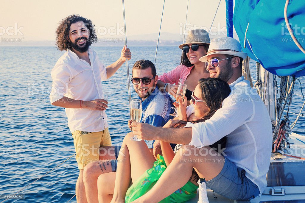 Group of happy friends with glasses champagne on yacht stock photo