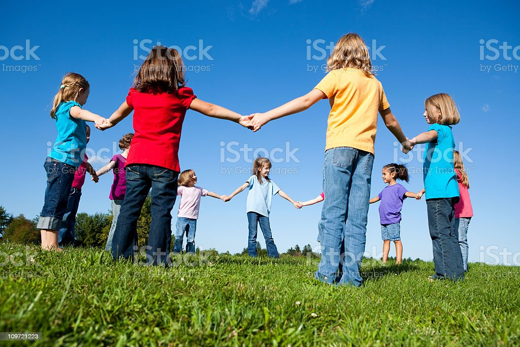 Group of Happy Girls Holding Hands in a Circle Outside royalty-free stock photo