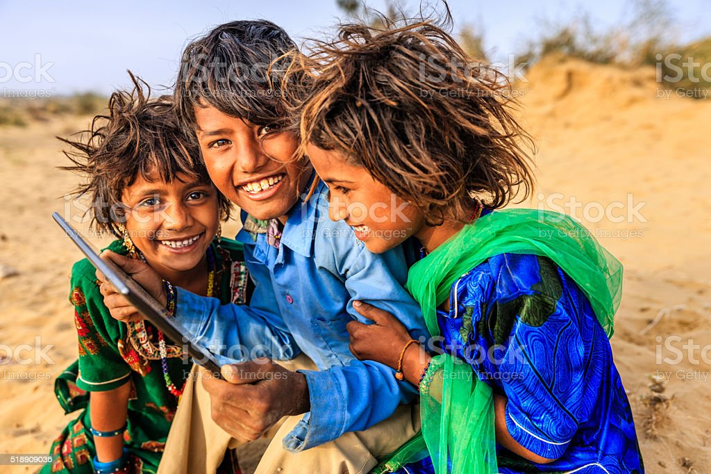 Group of happy Gypsy Indian children using digital tablet, India stock photo
