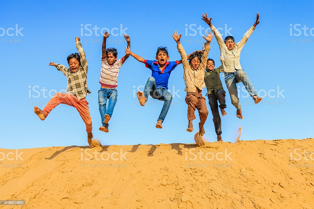 Group of happy Indian boys jumping off dune into sand stock photo