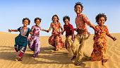 Group of happy Indian children running across sand dune, India