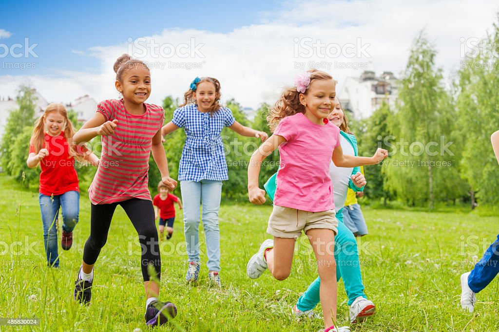 Group of happy kids running through green field stock photo