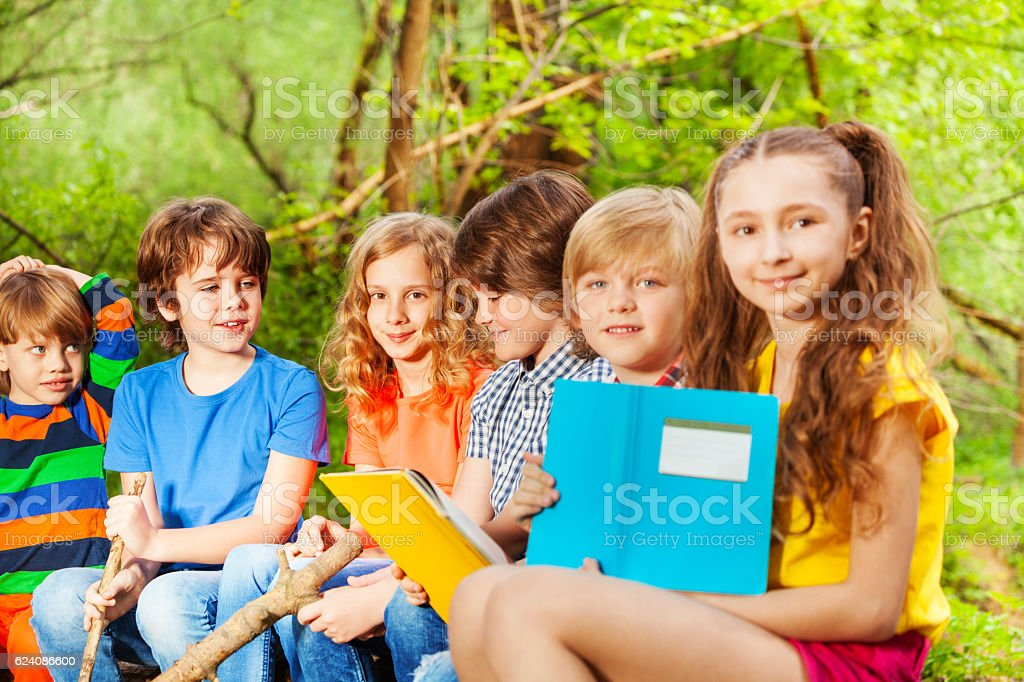 Group of happy kids sitting with books in the park stock photo