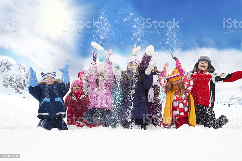 Group of happy kids throwing snow stock photo