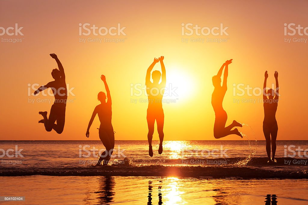 Group of happy people jumping in the sea at sunset stock photo