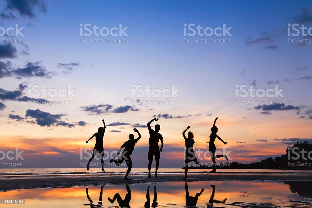 group of people jumping on the beach at sunset, silhouette of friends...