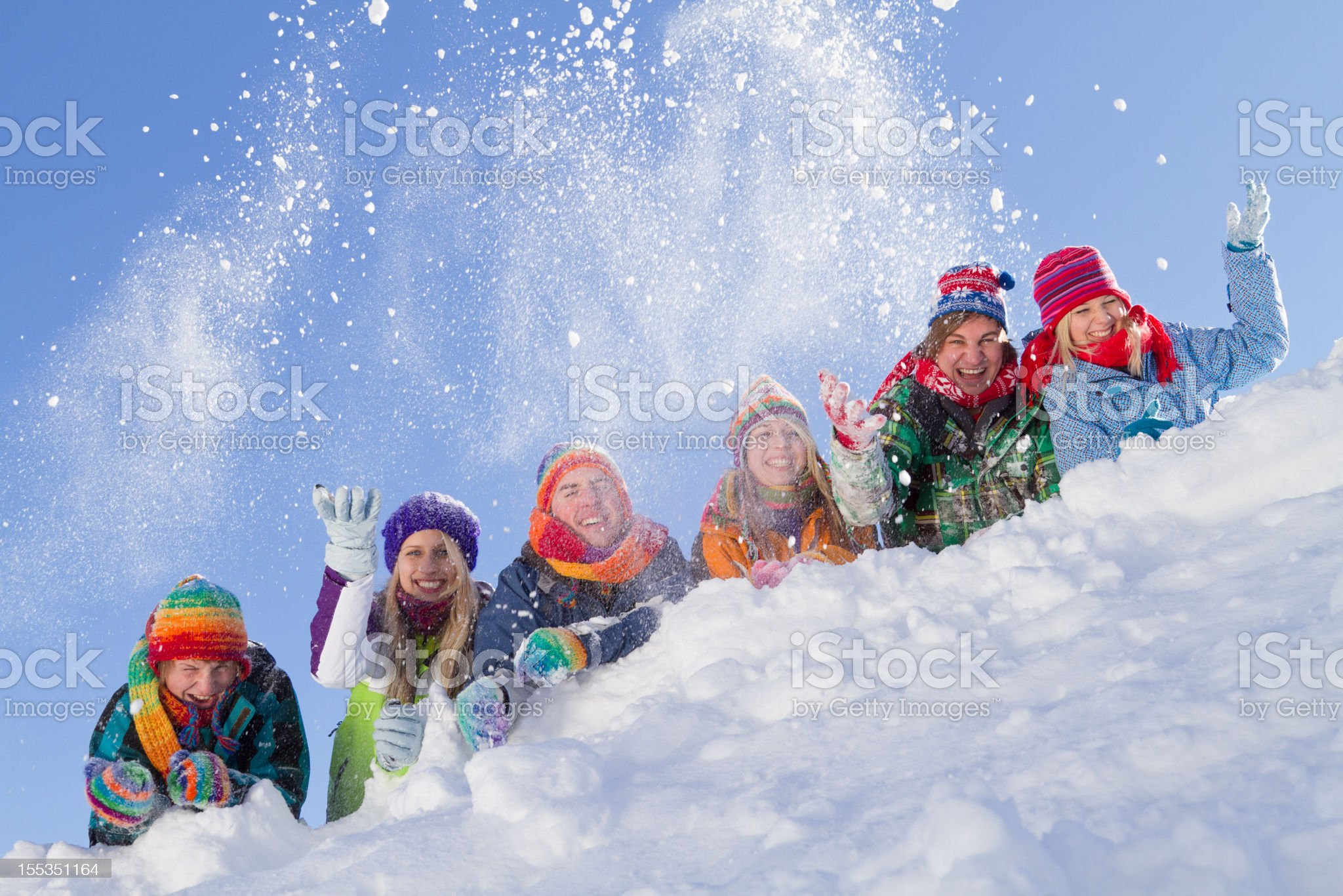Group of happy people lying on hill playing with snow royalty-free stock photo