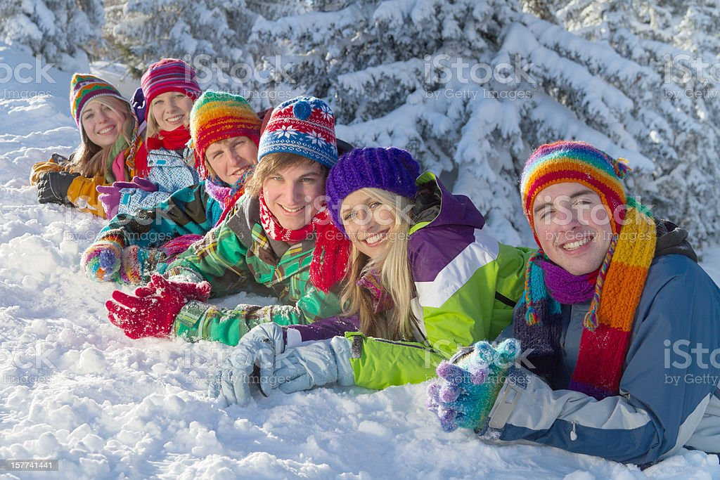 Group of happy people lying on snow in forest royalty-free stock photo