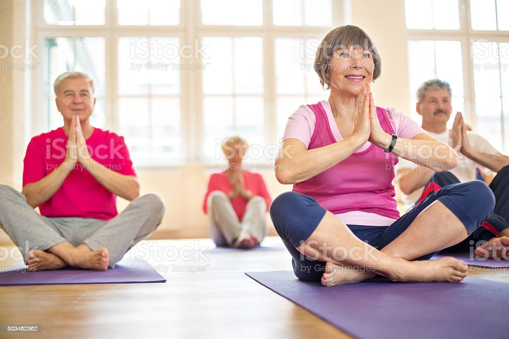 Group of happy seniors practising yoga stock photo