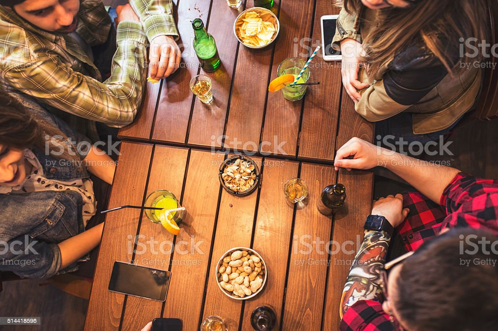 Group of happy smiling friends drinking beer and cocktails stock photo