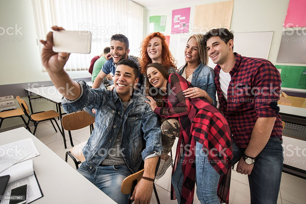 Group of happy students taking selfie in the classroom. stock photo