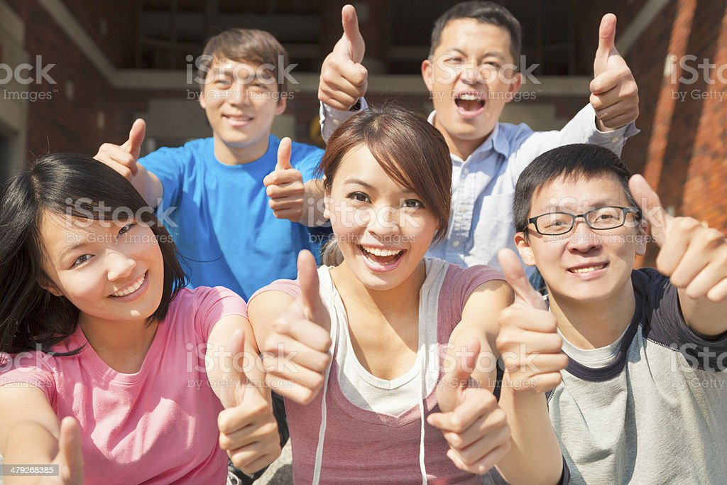 Group of happy students with thumbs up stock photo